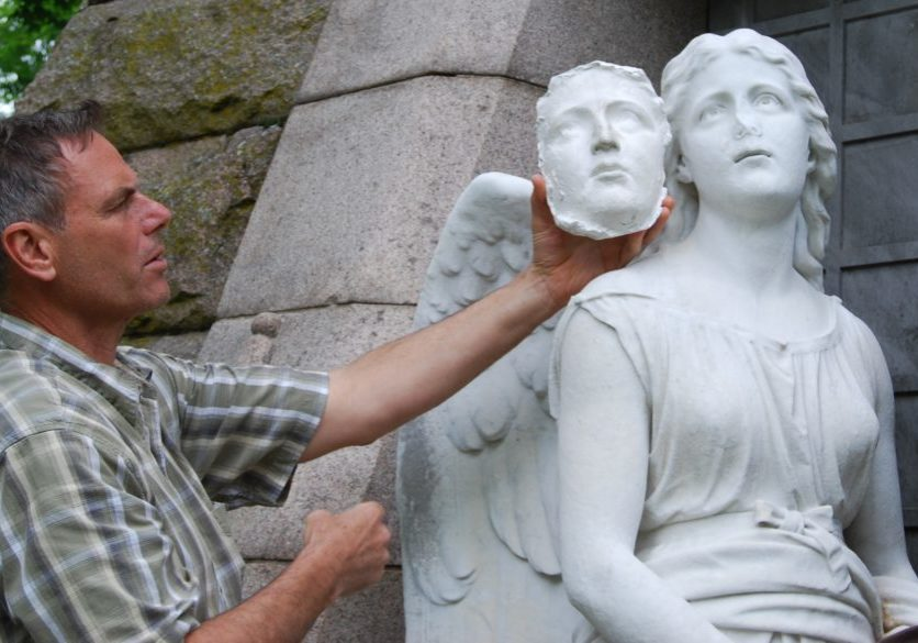 Conservator Francis Miller holds a model of the angel's face which will be used as a guide for the restoration of the damaged nose.